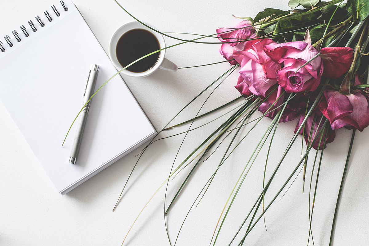 wedding planner, flowers and mug of coffee